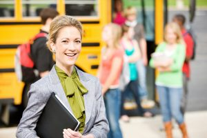 teacher outside with school bus