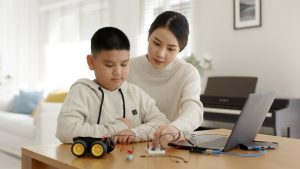 young student with their mother learning electronics