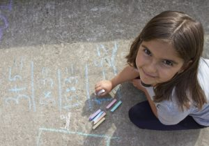 young girl doing math with chalk